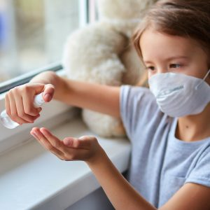 Little girl wear hygienic mask and press alcohol spray to protect, sanitizing.